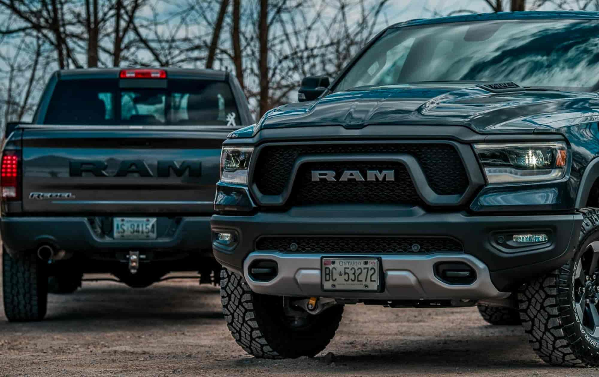 Two black dodge ram 1500s facing in opposite directions with bare trees in the background