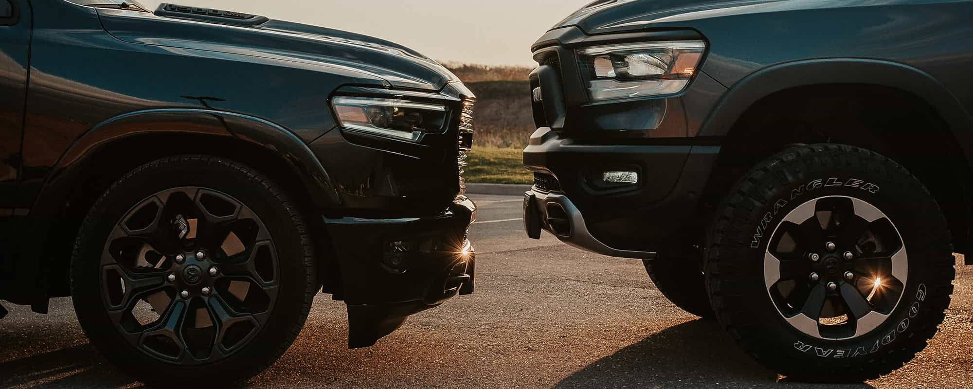 Two Ram 1500 trucks facing each other, one lowered truck on the left and one lifted truck on the right, on the street at sunset