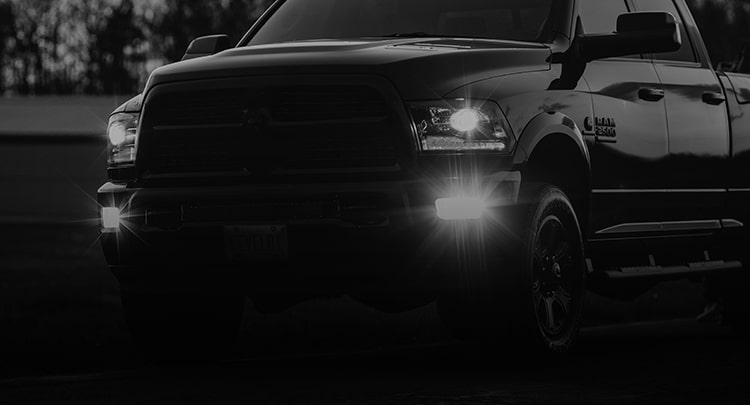 Dodge Ram 2500 diesel facing on an angle with aftermarket fog lights turned on