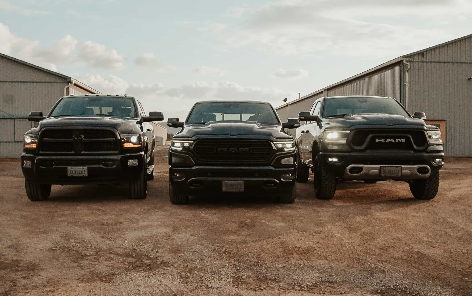 One upgraded Ram 2500 diesel truck on the left, one lowered Ram 1500 limited truck in the center, and one upgraded Ram 1500 Rebel truck on the right, in front of a warehouse